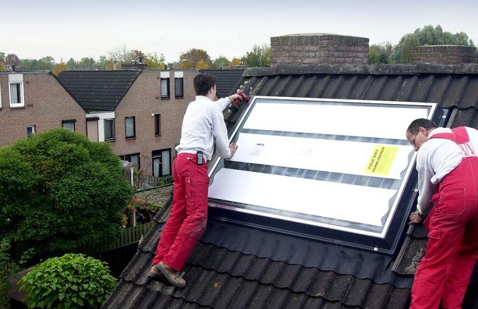 De plaatsing van zonnepanelen met boiler op een huis in Veghel.