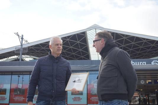 Ivo van Leeuwen (rechts) overhandigt Stan Sontrop het icoon van het monumentale stationsdak.