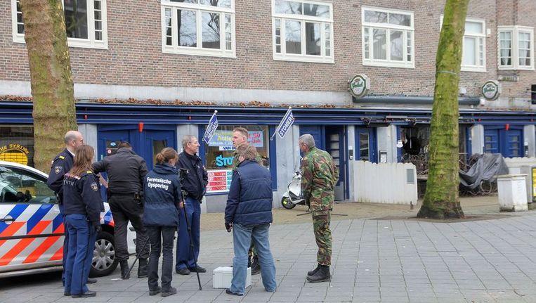 Politie en defensiepersoneel op het Van der Helstplein. Rechts café Belle Sud Beeld Het Parool