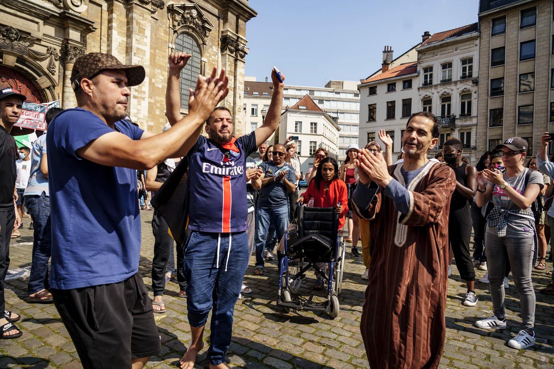 Hongerstakers komen opgelucht buiten aan de Begijnhofkerk in Brussel.  Beeld Eric de Mildt