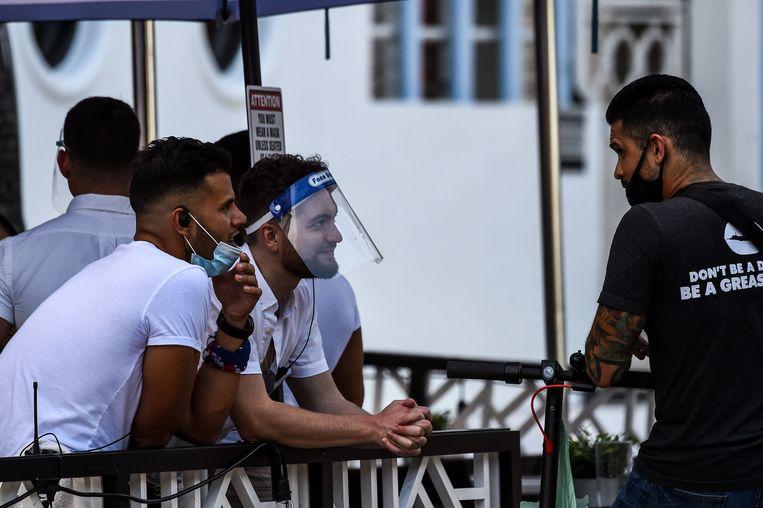 Mensen met een mondkapje en een gezichtsscherm wachten op hun bestelling in Florida. Beeld AFP