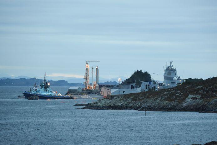 Het Noorse fregat KNM Helge Ingstad (rechts) na de aanvaring. Het marineschip helt al wat over.