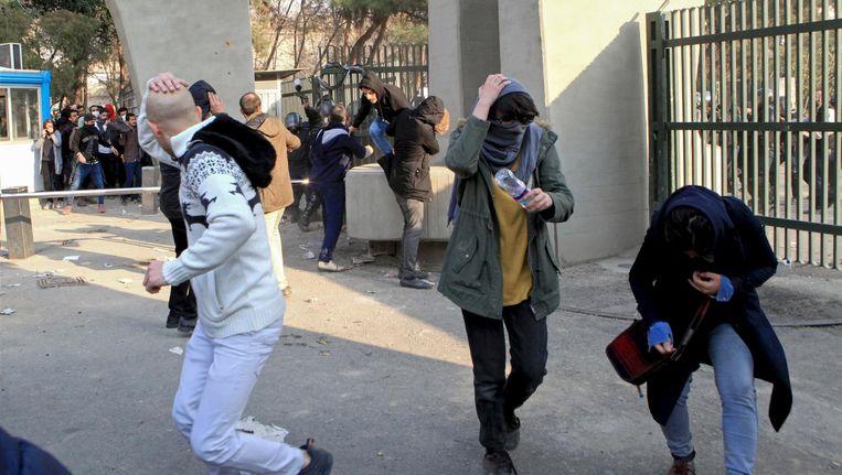 Studenten in Teheran rennen weg voor stenen die door de politie gegooid worden. Foto genomen door een persoon die niet voor AP werkt en verkregen buiten Iran. Beeld ap