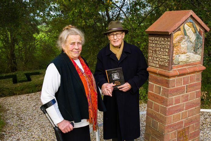 Rianne en Gerard Dubbeld met hun boek Het elfde gebod bij het oorlogsmonument in Alem. Bij het kruis in de haag op de achtergrond  werden in juni 1945 de lichamen gevonden van Jan en Tilly Klingen en Louis Boelen.