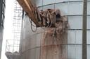 De ontplofte silo wordt leeggemaakt.