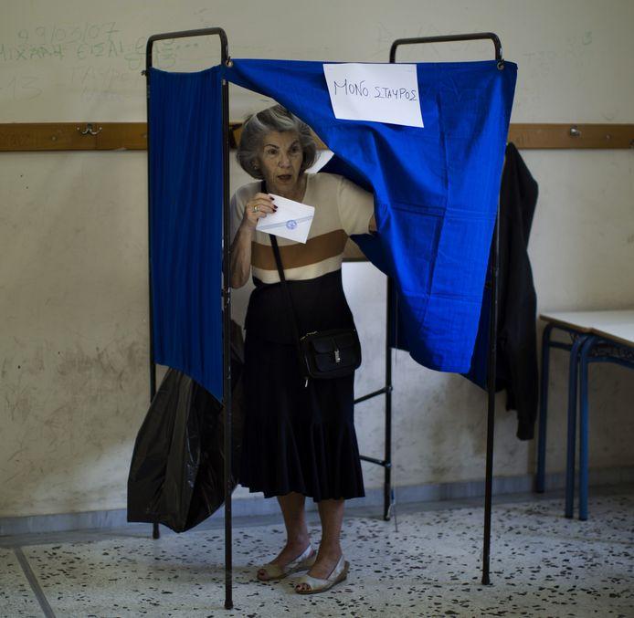 Een vrouw brengt haar stem uit in een stembureau in Athene. De Grieken beslissen vandaag of hun land al dan niet de voorwaarden van de kredietverstrekkers moet aanvaarden.