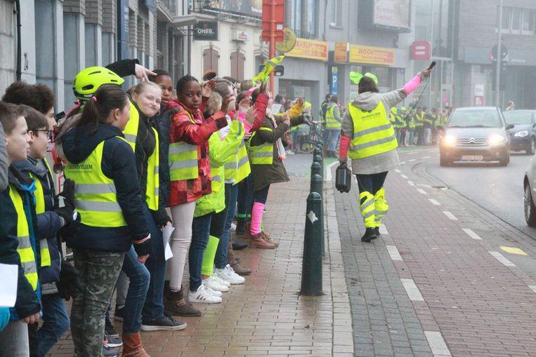 Leerlingen maken een fluoketting en scanderen voor meer verkeersveiligheid.