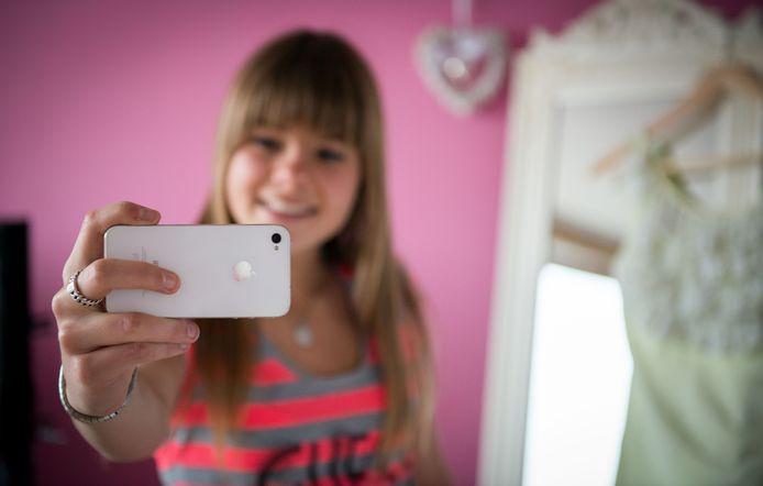 Een meisje maakt een selfie op haar slaapkamer.