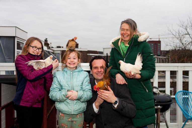 Roland van der Velde (52), Natalja Schoorlemmer (42) en hun kinderen Julia (11) en Olivia (8) hebben zes kippen. Beeld Renate Beense