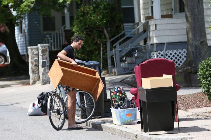 Schatzoeken bij het grofvuil lijkt universeel: deze Amerikaan pakt in Boston een kastje mee.