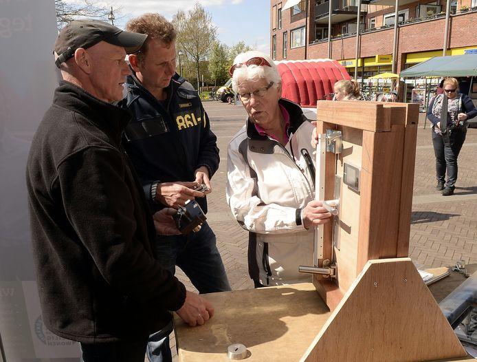 Een bezoekster van de veiligheidsmarkt op het Marktplein in Wijk en Aalburg laat zich bijpraten over de verschillende soorten hang- en sluitwerk.