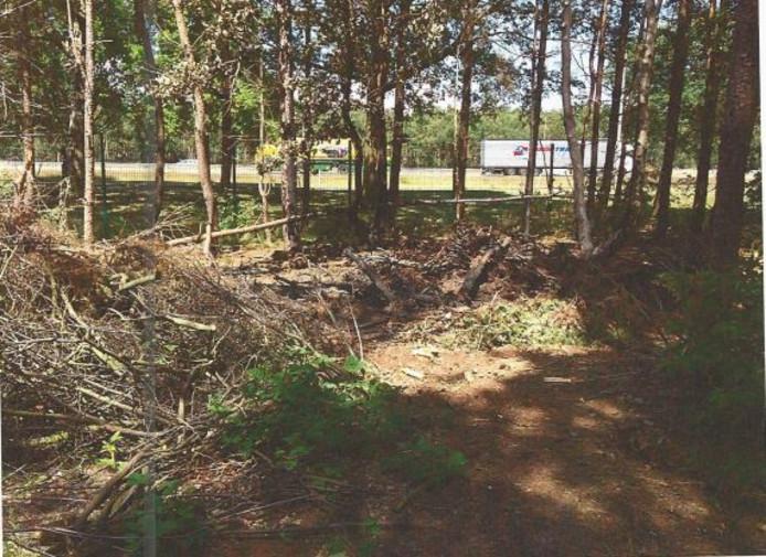 Een foto van de berg rommel, op de achtergrond de A58.