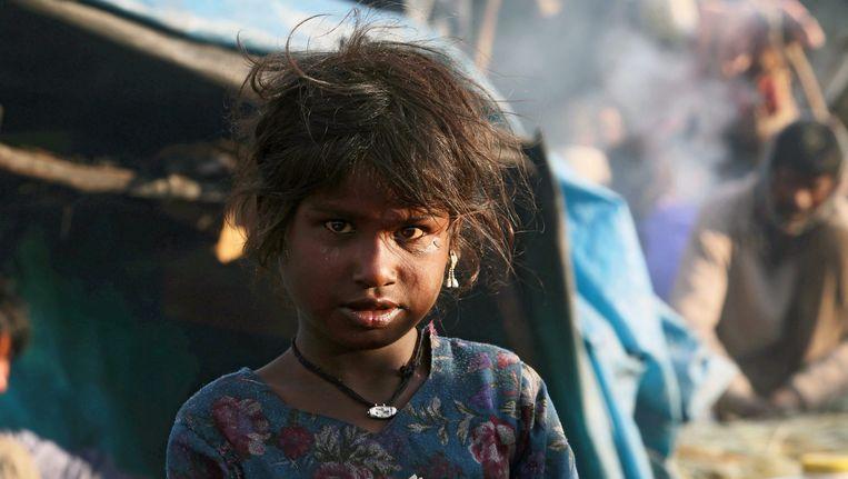 De dochter van een bezemfabrikant kijkt naar het werk van haar vader in de buitenwijken van Srinagar, India. Beeld EPA