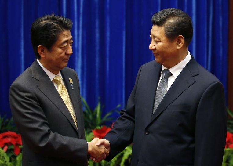 China's president Xi Jinping (R) schudt de hand van zijn Japanse evenknie, premier Shinzo Abe. Beeld Getty Images