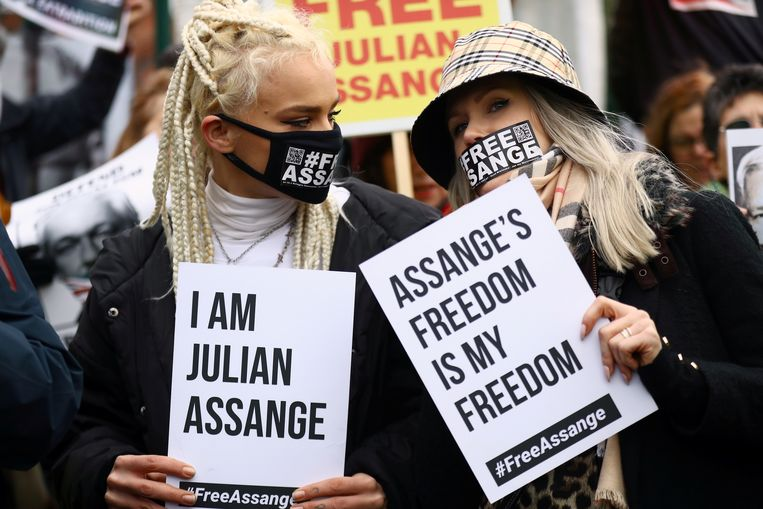 Medestanders van Assange steunen hem met bordjes buiten de rechtbank.