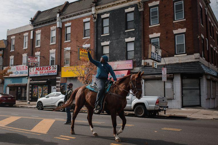 Een man gaat in Philadephia te paard over straat om mensen over te halen te stemmen tijdens de Amerikaanse presidentsverkiezingen. Beeld Bloomberg via Getty Images