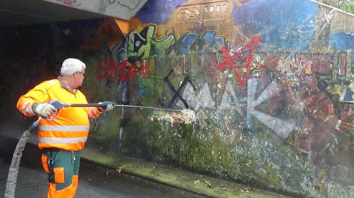 Een medewerker van de gemeente Apeldoorn verwijdert in september 2019 een van de aangebrachte hakenkruizen