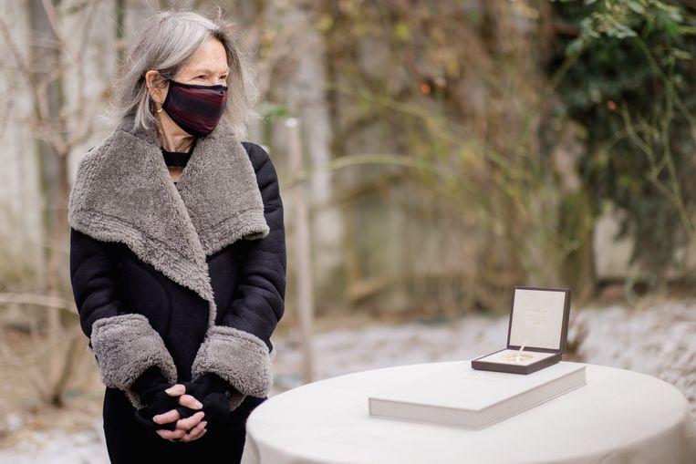 Louise Glück met de Nobelprijs-medaille in de tuin van haar huis in Cambridge in de staat Massachusetts.  Beeld EPA