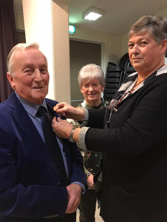 Kees de Munnik (l) krijgt het speldje voor zijn 70-jarige lidmaatschap van harmonie Nut en Uitspanning, uit handen van voorzitter Luci de Vlieger. In het midden zijn vrouw Janny.