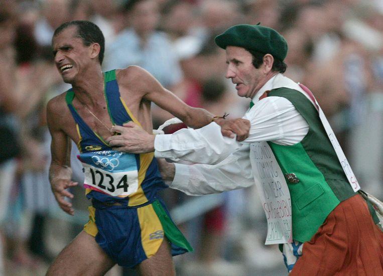 Vanderlei Cordeiro de Lima, leider in de marathon van Athene 2004, wordt de kant in geduwd door een geschifte ex-priester.  Beeld BELGAIMAGE