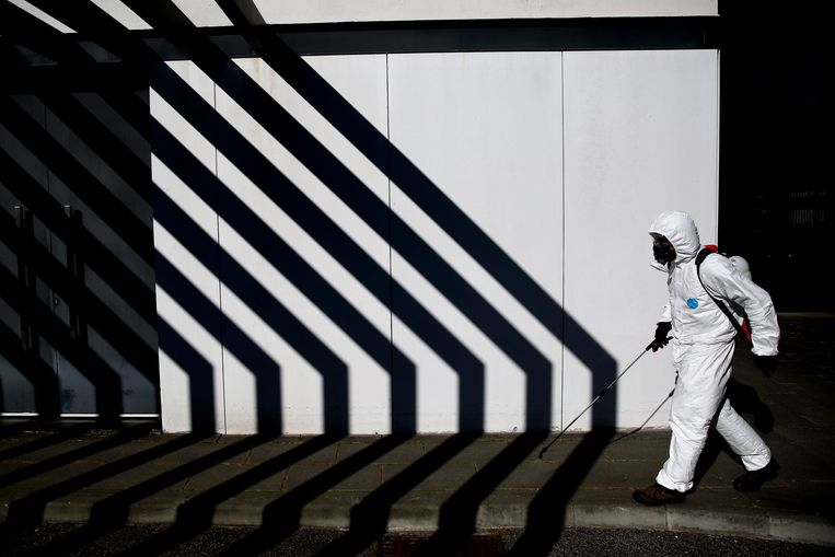 Een gemeentewerker ontsmet de stoep in de Portugese stad Cascais.  Beeld Photo News