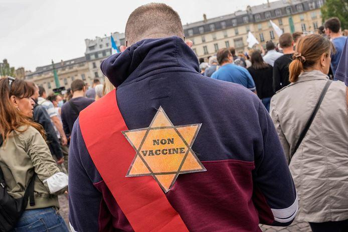 """Une étoile sur laquelle on peut lire """"non vacciné"""" est attachée au dos d'un manifestant anti-vaccination lors d'un rassemblement à Paris, samedi 17 juillet 2021. Une allusion aux étoiles que les Juifs ont été forcés de porter sous le régime nazi pendant la Seconde Guerre mondiale. D'autres manifestants portaient des pancartes évoquant le camp de la mort d'Auschwitz ou le régime d'apartheid d'Afrique du Sud, affirmant que le gouvernement français les persécute injustement dans sa lutte contre la pandémie."""