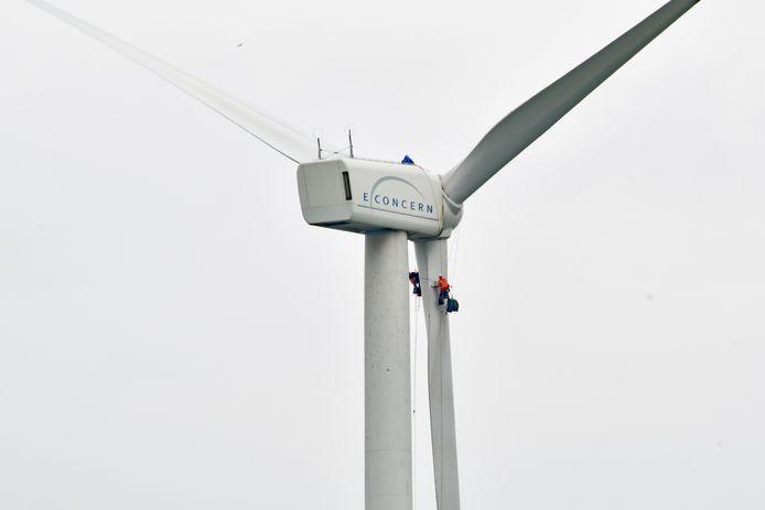 Van iets grotere afstand, twee mannen van Deutsche Windtechnik onder de gondel, de derde aan het werk op de gondel van één van de tweeëntwintig windturbines in de Terneuzense Koegorspolder.