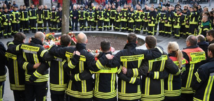 Brandweerlieden uit Augsburg herdenken hun collega op de plaats delict, twee dagen nadat hij werd doodgeslagen.