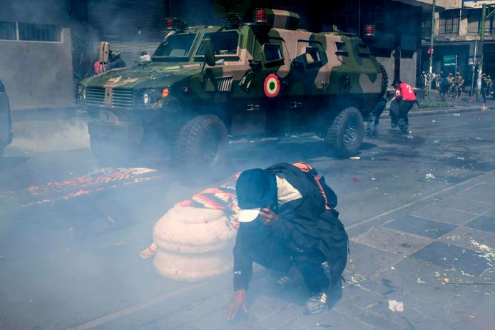 Een demonstrant met naast hem twee doodskisten probeert zich te beschermen tegen het traangas.