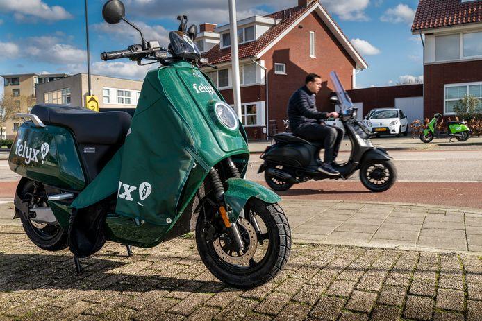 Op de Oude  Vlijmenseweg staat een Felyx-scooter tegenover een GO Sharing-scooter aan de overkant van de weg,