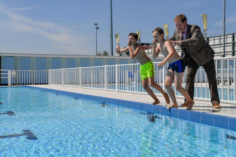 Sportschepen Luk De Mey geeft twee jongens een duwtje in het openluchtzwembad.