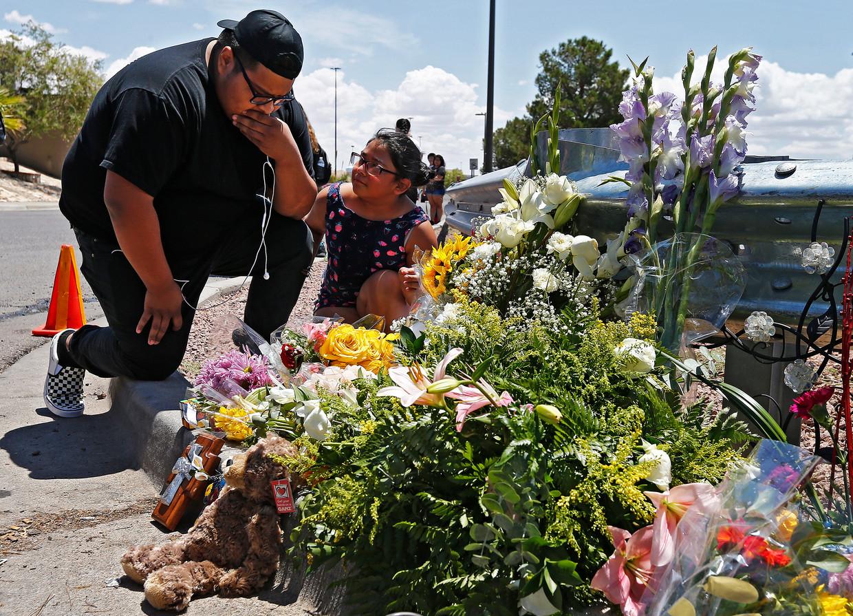 Mensen komen bloemen voor de slachtoffers leggen bij de Walmart in El Paso.
