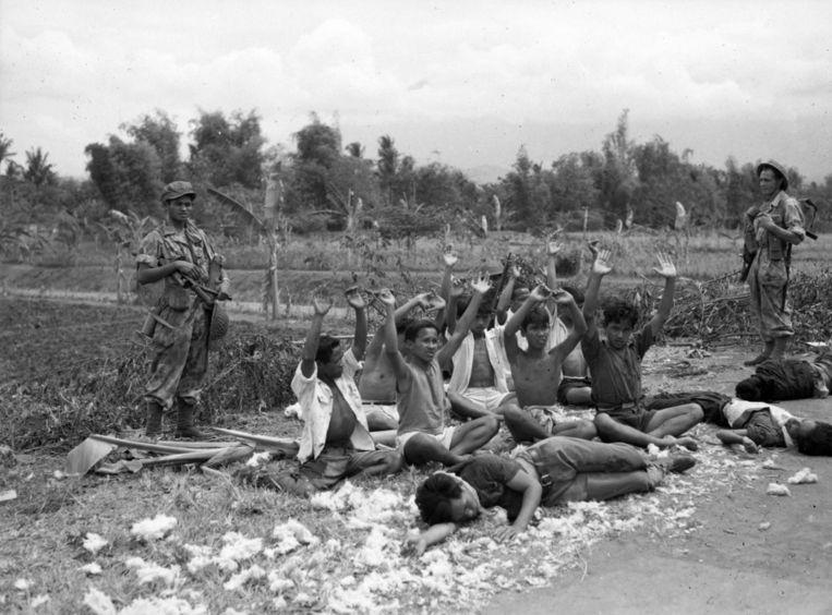 Foto die niet door de censuur kwam: Indonesiërs worden onder schot gehouden. Op de grond liggen doden en gewonden. Beeld Foto Nationaal Archief, uit boek van Louis Zweers