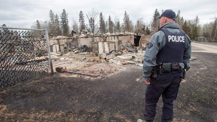 Een politieman aanschouwt een gebouw dat door de branden in Fort McMurray in de as werd gelegd.