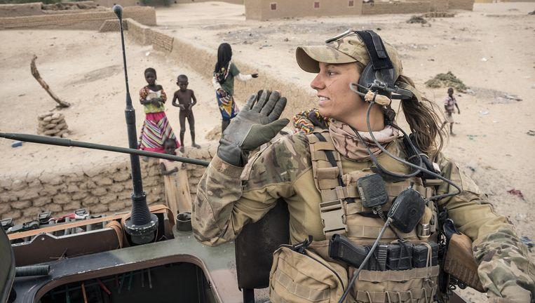 Een konvooi met leden van de Explosieven Opruimingsdienst trekt door een dorp niet ver van de rivier de Niger. De militair op de foto komt niet voor in het verhaal. Beeld Sven Torfinn