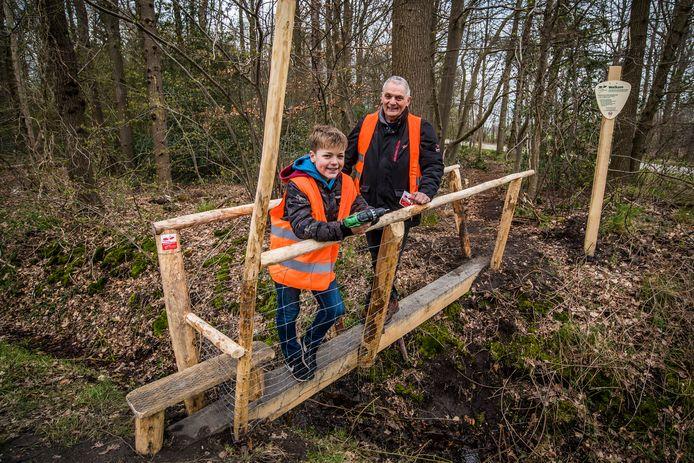 Vrijwilligers Henny van Doorn en kleinzoon Douwe Veldhuis op bruggetje dat speciaal voor het Reckense Markepad is gemaakt om bij 'de zes wegen' een particulier bosje in en uit te kunnen.