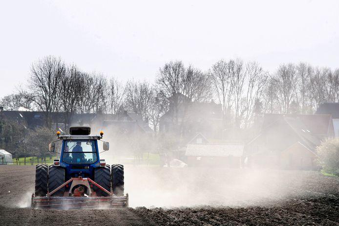 Door de droogte verdwijnt een tractor in de stofwolken tijdens het bewerken van het land.