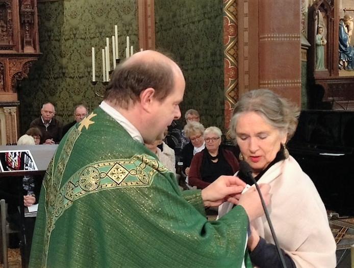 Pastoor Wil Smulders speld de Gregoriusmedalille op.
