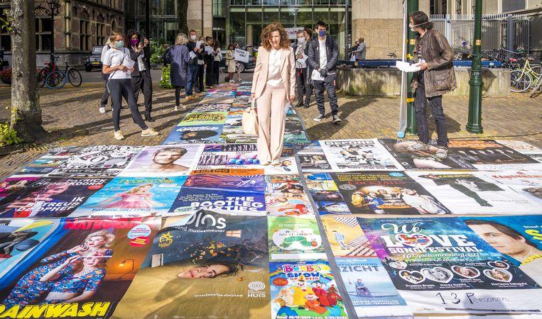 Minister Ingrid van Engelshoven (Cultuur) loopt over een loper, gemaakt van posters van alle voorstellingen en concerten die vanwege het coronavirus werden geannuleerd.  Beeld ANP/Lex van Lieshout