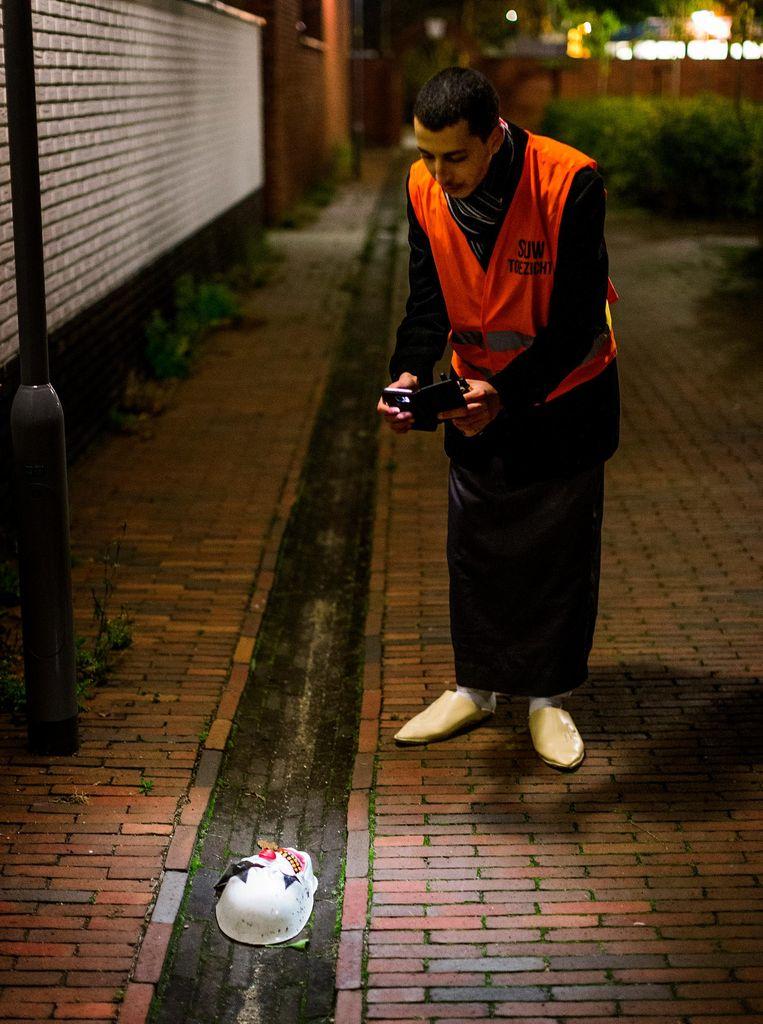 Mohammed Faris fotografeert een masker. Beeld Jiri Buller