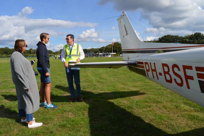Piloot Simon legt voor vertrek uit aan Mika Coenen (15, midden) en moeder Jacqueline Bohlken (49) hoe de staart van het vliegtuigje werkt.