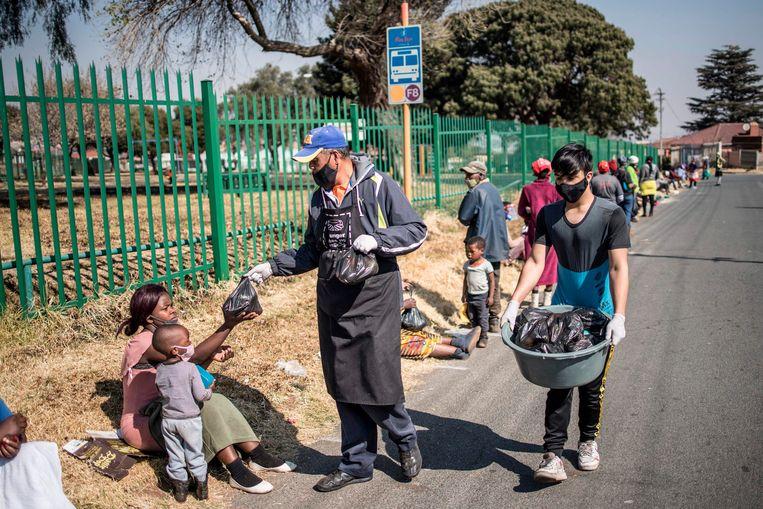 Vrijwilligers van de organisatie Hunger Has No Religion verdelen voedsel aan de arme inwoners van Johannesburg. Beeld AFP