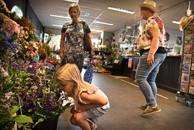Een meisje ruikt aan bloemen in een bloemenwinkel.  Beeld Marcel van den Bergh