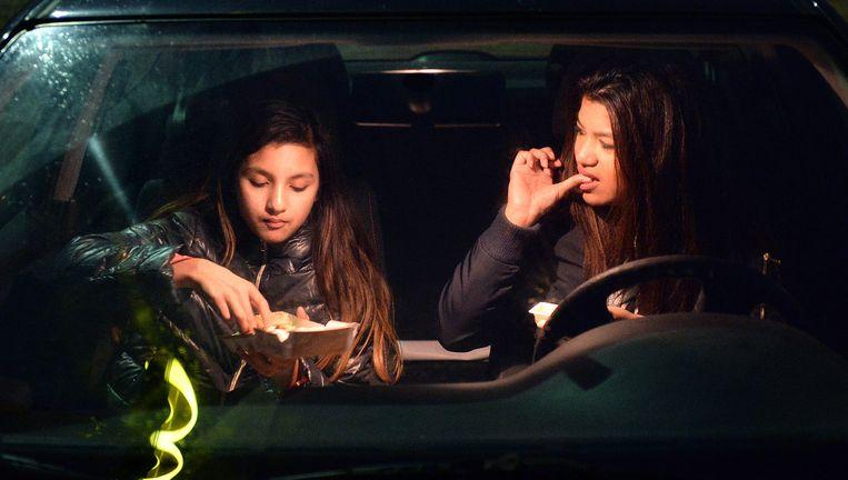 Sarah Slotman en haar dochter (links) eten eens per maand bij de McDrive in Tiel. Het is lekker snel en ze zijn er eens even mee van huis. Beeld Marcel van den Bergh