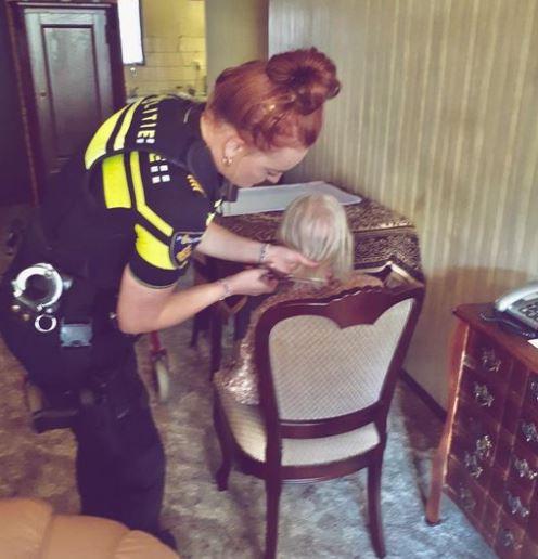 Een agent knipt het haar van de vrouw.