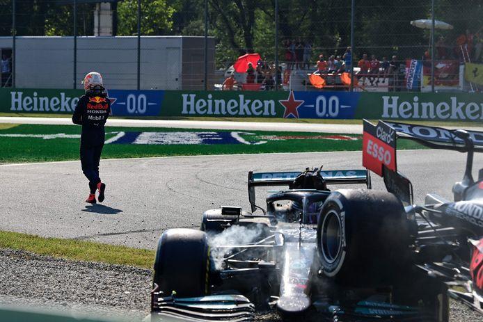 Max Verstappen loopt op de achtergrond weg na de crash met Lewis Hamilton, die hier nog in zijn Mercedes zit.