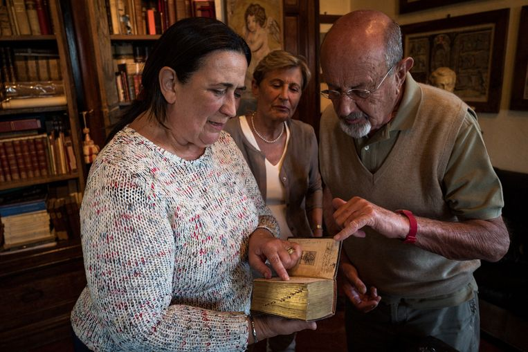 Raffaella Paoletti showing to a couple of guest visiting the castle a book with different 'titles' used in the past to refer to professional people Nicola Zolin Beeld Nicola Zolin