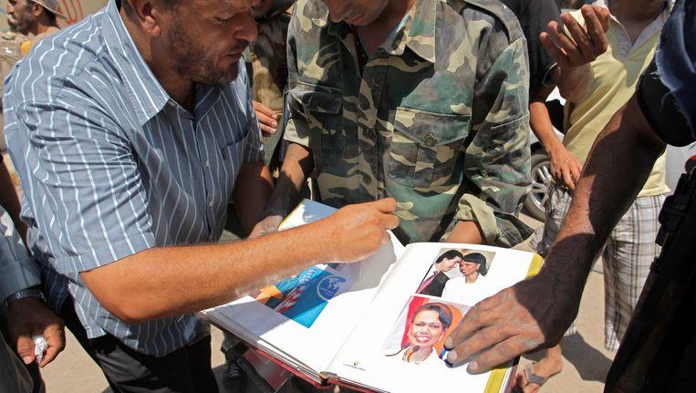 Opstandelingen bladeren door het in de kamers van Kaddafi gevonden fotoboek van Rice Beeld AP