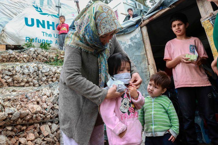 Een vrouw helpt een kind met een van de geïmproviseerde maskers die werden uitgedeeld aan migranten in het kamp Moria op Lesbos. Beeld AFP