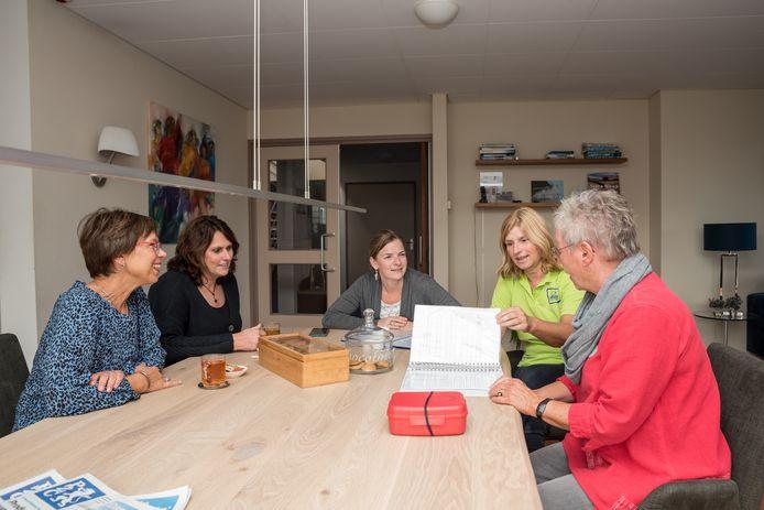 De tafel in de huiskamer is dé ontmoetingsplek in het Kaaskenshuis. Daar komen vrijwilligers, familieleden en andere betrokkenen samen. Vlnr: Coördinatrices Anita Joziasse en Liset Padmos, zorgvrijwilligster Annemarie Cats, verpleegkundige Anita Zandee en zorgvrijwilligster Marga van Dijck.